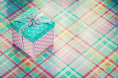 Wrapped present box on checked fabric background holidays concep