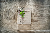 Handmade gift box wrapped in brown paper with green branch on wo