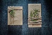 Handmade present boxes with thuya branch on black background cel