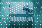 Gift box with ribbon on blue polka-dot background holidays conce