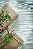 Handmade boxed present with green branch on wooden board vertica