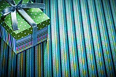 Gift in cardboard box on striped background holidays concept