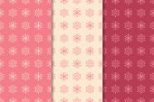 Snowflakes patterns. Set of cherry red seamless backgrounds with christmas elements