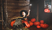 Halloween.  little witch   conjures with  book of spells,  magic wand and pumpkins