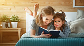 happy family mother and daughter reading book in bed