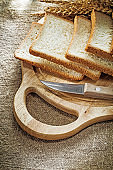 Carving board kitchen knife sliced bread wheat ears on sacking b