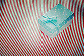Wrapped gift box on red striped tablecloth celebrations concept