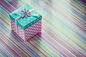 Wrapped gift box on stripy fabric background celebrations concep
