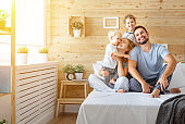 happy family mother father and children daughter and son in bed