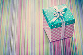 Wrapped gift box on stripy fabric background holidays concept