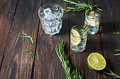 Alcoholic drink - gin tonic cocktail - with lime, rosemary and ice on rustic wooden