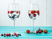 Refreshing cocktail with vodka martini with ice and berries on wood table