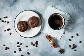 Chocolate cupcakes with a cup of hot black coffee on cocrete background.