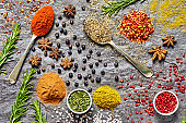 Flat lay of various Indian herbs and spices on slate