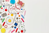 Overhead flat lay of colorful sewing items on white background