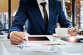 Young business man working at office with tablet,calculator,post