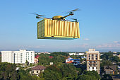 Drone with cargo container flying over the town.