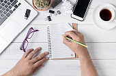business hand man writing on blank notebook on table,