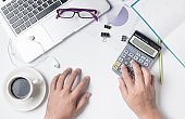 business man using calculator on modern white office desk table