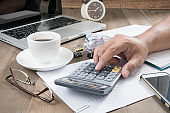 business man using calculator with hot coffee