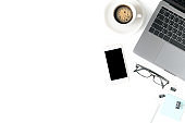 Desk with laptop, eye glasses, notebook and a cup of coffee isolated