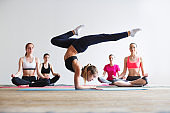 Young woman doing exercise standing on hands.