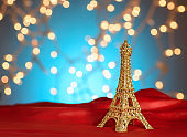 Valentine's Day in Paris. Christmas, New Year in Paris. Golden Eiffel Tower on bright red satin. Blurred Xmas lights background. Copy space.