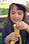 Attractive caucasian brunette child with long hair, in blue t-shirt and white cap eating banana and smiles on a picnic in park.