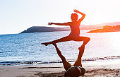 Silhouette of fit couple doing acro yoga outdoor on the beach - Woman and man training at sunset in nature - Focus on bodies - Healthy lifestyle and zen concept