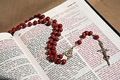 wooden rosary with a crucifix between the pages of the Bible with the psalm 'Love to the enemies'