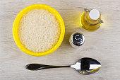 Plastic bowl with dry rice, vegetable oil, salt, metallic spoon