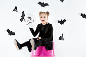 Little girl witch in black dress over magical accessories. Halloween, the studio evening