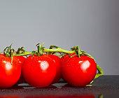 The fresh cherry tomatos on gray background