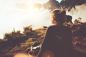 Woman hipster hiking in the wild at sunset