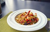 Spaghetti with Thai Spicy Herbal Sauce and prawns on white plate