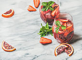 Fruit refreshing Sangria cocktails with ice and mint, copy space