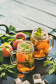 Summer refreshing cold peach ice tea on table, copy space