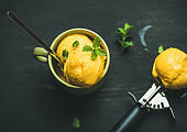 Mango sorbet ice cream scoops with mint, top view