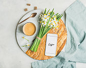 Cup of morning coffee, bucket of flowers and mobile phone