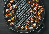 Roasted chestnuts in grilling pan over dark scorched wooden background