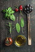 Vegetables and herbs on dark rustic wooden background. Greek black olives, fresh green sage, rosemary, basil herbs, oil, tomato