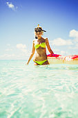 Blonde woman standing in shallow water with snorkel equipment, Maldives