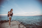 Young woman backpacker on the beach