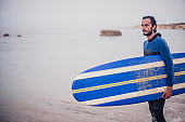 Charming surfer on the beach