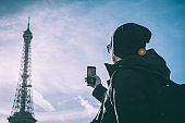 Young man in front of Eiffel Tower making photograph