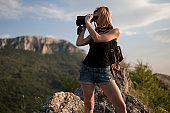 Woman with binoculars on mountain top