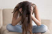 Depressed teenager having problems, stressed woman holding head in hands