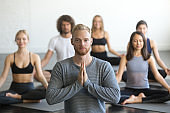 Group of young sporty people in Sukhasana pose