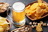 Lager beer and snacks on stone table