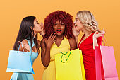 Three happy women after shopping. Afro american, asian and caucasian races. Shopping with isolated on orange background on black friday holiday. Concept for sale advertisement.